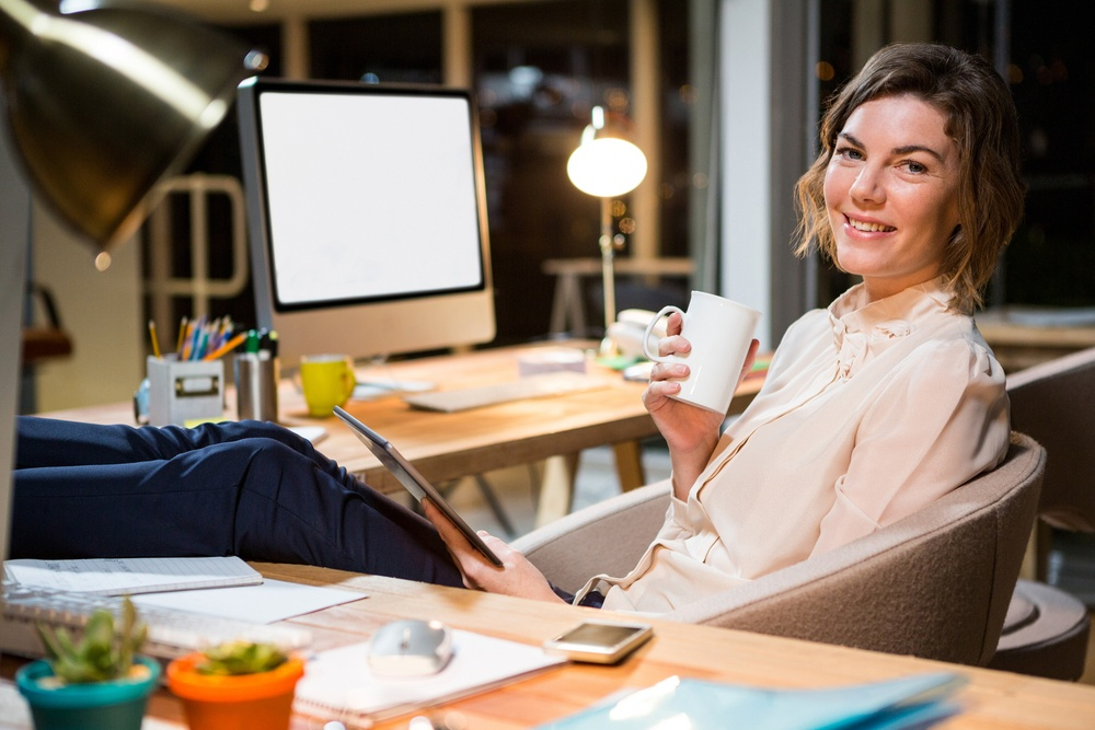 Portrait of businesswoman holding digital tablet and coffee cup at her desk in the office.jpeg